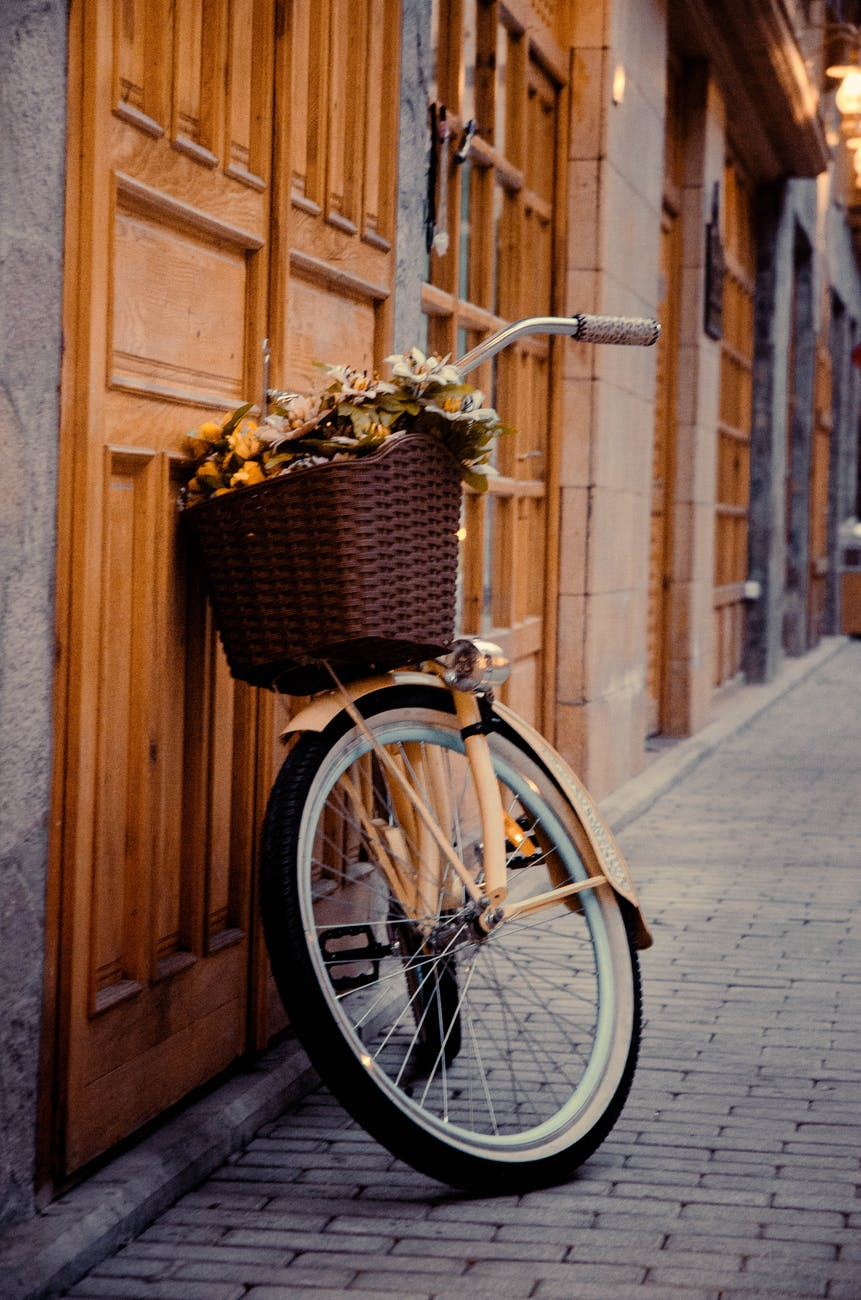 photo of bicycle parked beside wooden door